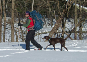 In winter, a BIG backpack like this Osprey Argon 110 is needed to carry all your gear. Not nearly so useful is Chester, the dog, who is about to step on the back of his master's snowshoe . . .