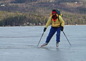 Jamie Hess wears two hats and mittens with liners on a cold day of skating on Lake Sunapee.  His cross-country ski boots are warm with thick socks beneath.