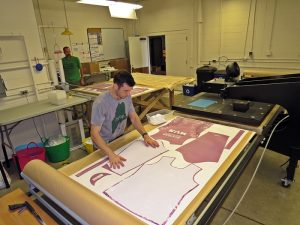 With owner Jeremy Litchfield looking on in the background, one of Atayne's workers sets up a bike jersey's sublimated graphics. (EasternSlopes.com)