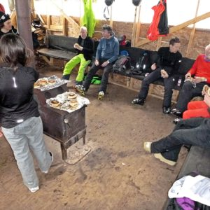 A bunch of happy skiers refueling on brie & ham bagels and enjoying the warm stove, reliving the morning runs and recharging for the afternoon excitement. (EasternSlopes.com)